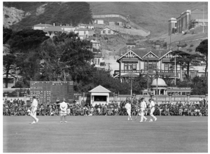 The photograph was taken at the Basin Reserve in January 1930. It was a great day for New Zealand cricket. Batting first the New Zealand openers put on 276 for the first wicket, for many years a New Zealand record, and the scoreboard shows the moment when both openers reached their centuries. In the background above the Basin work is just beginning on the car tunnel, while to the right the north wing of the Wellington Girls' College building hall is nearly complete. Outside the ground a tram advertising soap rumbles along Dufferin Street, between the Wakefield Memorial and the long-demolished houses on the other side. The scoreboard and the little scorers' shed in the northeast corner had been erected a few years before. Nowadays the scoreboard is on the southern side. (Photo: G-2-¼-EP, Alexander Turnbull Library).