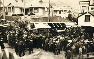 Tram accident on the corner of Pirie and Brougham Streets, Mount Victoria, showing crowds surrounding the scene and a police van at left. Photograph taken January 1920 by an unknown photographer. National Library of New Zealand PAColl-D-0927-2