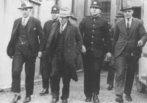 George Coats, flanked by police, was convicted of murdering Phyllis Symons in 1930 and burying her in earthworks at the construction of the Mt Victoria tunnel
